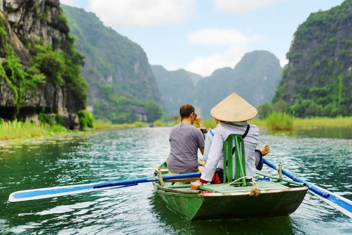 Tourists+traveling+in+small+boat+along+the+ngo+dong+river+at+the+tam+coc+portion,+ninh+binh+province,+vietnam.